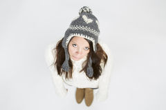 Sad girl in winter pullover and cap looking up. Royalty Free Stock Image