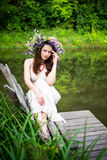 Sad girl in a wreath sits on bench Royalty Free Stock Images