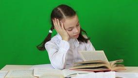Sad girl writing, reeding. Child doing homework stock video footage