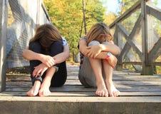 Sad girls sitting on bridge. Two barefoot girls - sad crying kids sitting on wooden bridge royalty free stock image