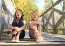 Sad girls sitting on bridge. Two barefoot girls - sad crying kids sitting on wooden bridge stock image