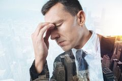 Sad gloomy man making difficult decision. Painful thoughts. Tired sad office manager sitting with his eyes closed while making a very difficult decision Stock Photo
