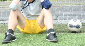 Sad goalkeeper. Goalkeeper sits Annoyed because of a missed goal Royalty Free Stock Photos