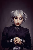 Sad gothic girl. Pretty old-fashioned gothic girl posing over dark background stock photography