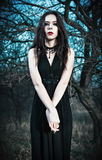 Sad gothic girl stands among autumnal trees Stock Photo