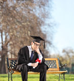 Sad graduate student sitting on a bench in park Stock Image