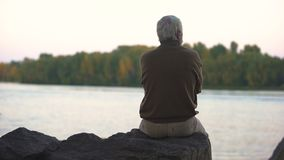 Sad grandfather sitting river bank back view, old age loneliness, peaceful rest. Stock footage stock video footage