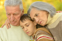 Sad grandparents with boy in park Royalty Free Stock Images