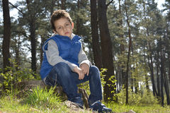 The sad  green-eyed boy sitting in the woods. Stock Photos
