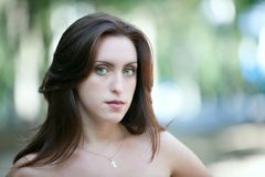 Sad green-eyed girl. With a cross worn on the neck Stock Photos