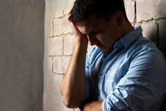 Sad guy against wall Stock Photo
