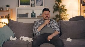 Sad guy drinking alcohol crying wiping with tissue sitting on sofa watching TV. Sad guy is drinking alcohol crying and wiping face with paper tissue sitting on stock video footage