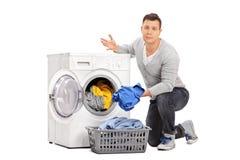 Sad guy emptying a washing machine Royalty Free Stock Images