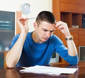 Sad guy fills out financial documents at table in home interior Royalty Free Stock Images