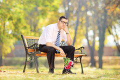 Sad guy holding a bouquet of flowers on a bench in a park stock photography