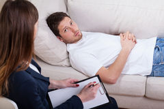 Sad guy at psychotherapist room Royalty Free Stock Image