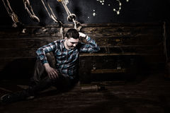 Sad guy sits near a chest, holding glass bottle and trying to ge Royalty Free Stock Photo