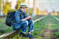 Sad guy sits on a railway in the evening Stock Image