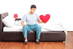 Sad guy sitting alone on bed and holding a heart Stock Photos