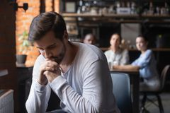 Free Sad Guy Sitting Alone Separately From Other Mates In Cafe Royalty Free Stock Images - 145994589