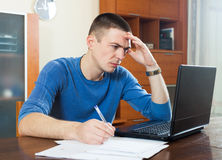 Sad guy staring at financial documents in laptop at table in hom Royalty Free Stock Images