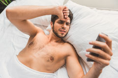 Sad guy using smartphone in bedroom stock photos