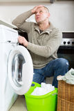 Sad guy using washing machine Royalty Free Stock Images