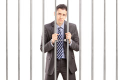 Sad handcuffed businessman in suit posing in jail and holding ba. Rs, isolated on white background Stock Photos