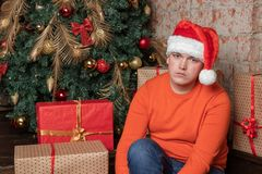 Sad handsome guy in santa claus hat is sitting under the tree surrounded by boxes of gifts. Christmas and gifts royalty free stock images