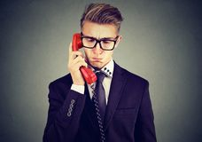 Sad handsome man having unpleasant telephone conversation looking down royalty free stock image