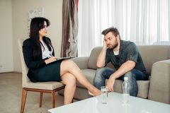 Sad hasband at psychologist, psychology support. Sad hasband at psychologist, professional psychology support. Female doctor gives consultation to male patient Royalty Free Stock Photo