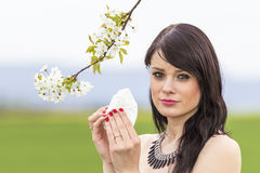 Sad hayfever girl in spring nature with blossom branch. The beautiful young woman is pained by her allergy every year. She holds a tissue in her hands Stock Image