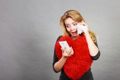 Sad heartbroken woman looking at her phone. Betrayal, bad relationship, hurt love concept. Sad heartbroken woman crying and looking at her phone Royalty Free Stock Photos