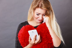Sad heartbroken woman looking at her phone. Betrayal, bad relationship, hurt love concept. Sad heartbroken woman crying and looking at her phone royalty free stock images