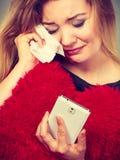 Sad heartbroken woman looking at her phone. Betrayal, bad relationship, hurt love concept. Sad heartbroken woman crying and looking at her phone Royalty Free Stock Photo