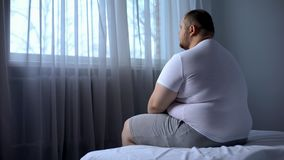 Sad heavy man sitting on bed at home, health problem, depression, insecurities. Stock photo royalty free stock photography