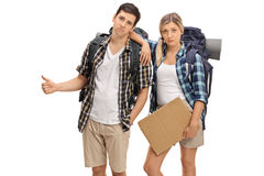 Sad hikers holding a blank cardboard sign and hitchhiking Stock Images