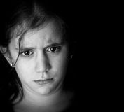 Sad hispanic girl on a black background Royalty Free Stock Images