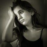 Sad hispanic girl sitting in a corner stock photo