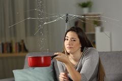 Sad homeowner with a bad insurance concept. Sad homeowner with water leaks and a broken umbrella sitting on a couch in the living room at home. Bad insurance Stock Photos