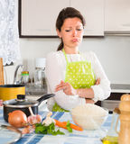 Sad housewife cooking dinner Stock Photo