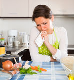 Sad housewife cooking dinner. Upset woman in apron cooking dinner for her family at home kitchen Royalty Free Stock Image