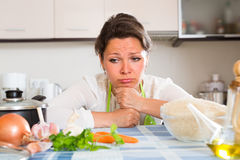 Sad housewife cooking dinner Royalty Free Stock Photos