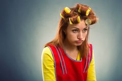 Sad housewife with curlers on her hair Royalty Free Stock Photos