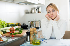 Sad housewife with documents in kitchen Stock Images
