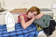 Sad housewife ironing shirt lazy at home kitchen using iron lean Royalty Free Stock Images