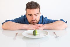 Sad and hungry man watching poor diet meal royalty free stock photos