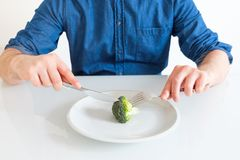 Sad and hungry man watching poor diet meal. Depressed man dieting and eating only vegetables stock photography