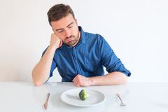 Sad and hungry man watching poor diet meal stock image