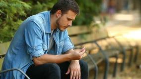 Sad husband after divorce. Closeup of a sad husband complaining after divorce holding the wedding ring in a park
